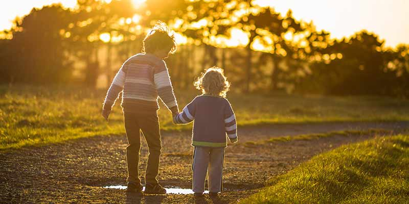 Two young brothers walking down a dirt path in the outdoors at sunset.