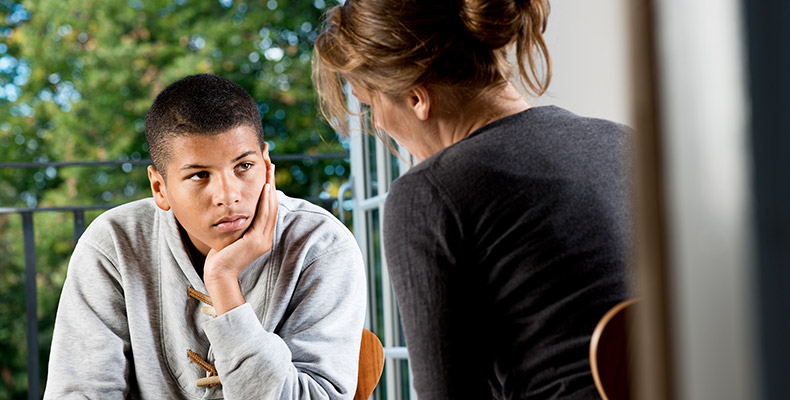 Woman talking with a teenage boy.